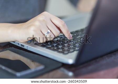 A Female(woman) finger on the enter key - stock photo