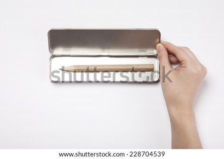 A female(woman, girl) hand hold a empty iron(stainless) pencil case isolated white, top view. - stock photo