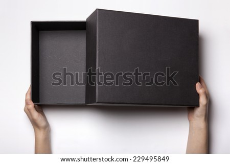 A female(woman, girl) two hands hold and open the empty(blank) black box isolated white, top view at the studio. - stock photo