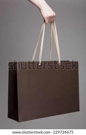 A female(woman) hand hold a brown shopping bag(paper bag) and ivory strings at the studio. - stock photo