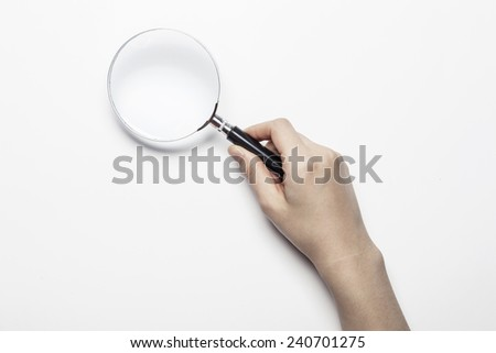 A female(woman) hand hold a magnifier(reading glass) isolated white at the studio. - stock photo