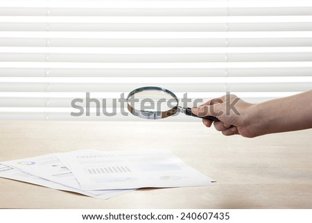 A female(woman) hand hold a magnifier(reading glass) point to graph paper(document) on the office desk(table) behind white blind. - stock photo