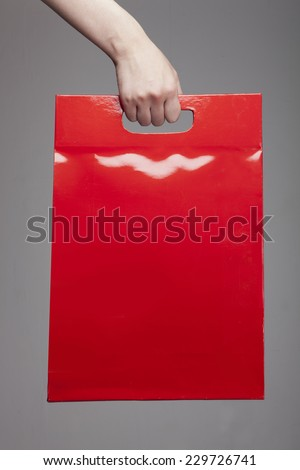 A female(woman) hand hold a red shopping bag(paper bag) at the studio. - stock photo