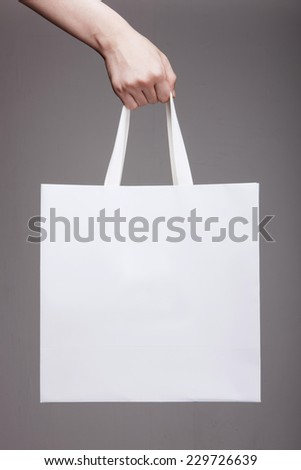 A female(woman) hand hold a white shopping bag(paper bag) and white strings at the studio. - stock photo