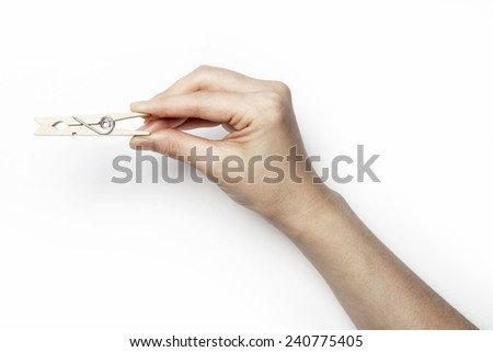 A female(woman) hand hold a wood clothespin isolated white at the studio.  - stock photo