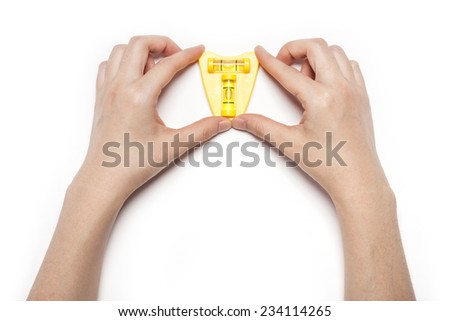 A female(woman) hand hold the level isolated white, top view at the studio.