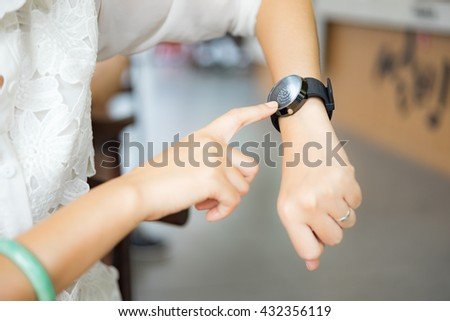 A female(woman) hand hold(touch) a smart watch on her left hand. - stock photo