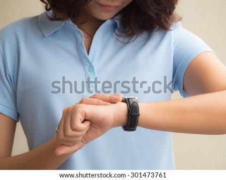 A female(woman) hand hold(touch) and looking at smart watch.