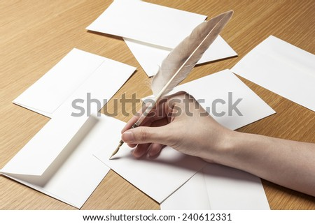 A female(woman) hand hold(write) a feather quill pen on the envelopes and wood desk(table) top view at the studio. - stock photo