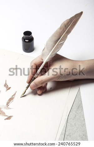 A female(woman) hand hold(write) a feather quill pen on the letter and envelope. - stock photo