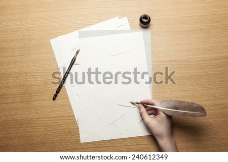 A female(woman) hand hold(write) a feather quill pen with ink on the letter paper and wood desk(table) top view at the studio. - stock photo