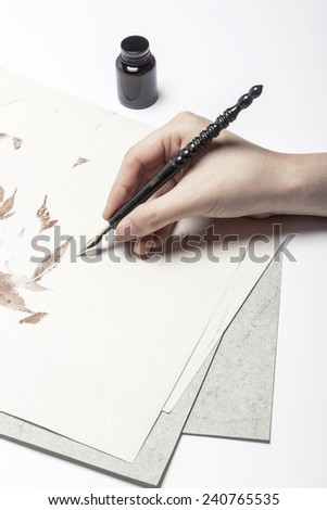 A female(woman) hand hold(write) a fountain pen on the letter and envelope. - stock photo