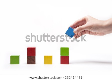 A female(woman) hand pick up(hold) a wood block among Color wood cube blocks(yellow, red, blue, purple) like bar graph symbolizing sales growth isolated white at the studio. - stock photo