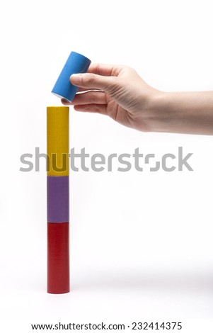 A female(woman) hand pick up(hold) a wood block among many color(red, yellow, blue, purple) wood blocks like bar graph symbolizing sales growth isolated white at the studio. - stock photo