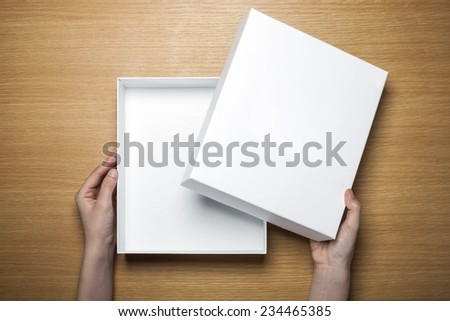 A female(woman) hands hold a empty(blank) white box on the desk(table) top view at the studio. - stock photo