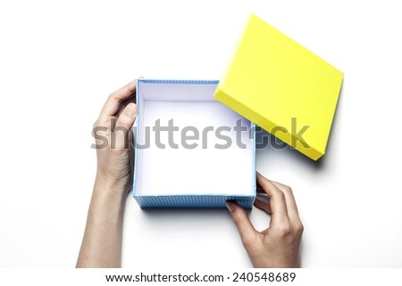 A female(woman) hold(open) a empty(blank) present box(yellow, blue) isolated white at the studio. - stock photo