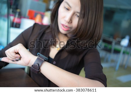 A female(woman) looking at her smart watch.