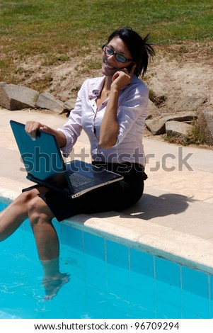 A female working on a pool edge and talking in a mobile phone - stock photo