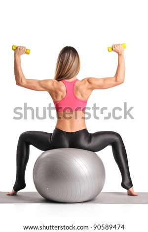 A female working out with dumb bells while sitting on a pilates ball isolated on white background - stock photo