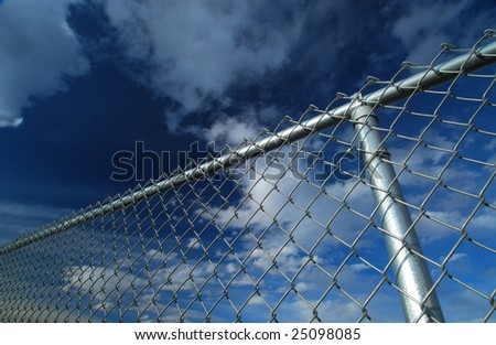 A fence and fence post against an evening sky.  Freedom is on the other side! - stock photo