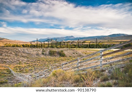 A fence crosses the high prairies of the Colorado Rockies - stock photo
