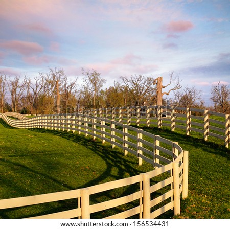 A Fence Line And Green Grass In The Morning During Springtime In Horse Country, Lexington, Kentucky, USA - stock photo