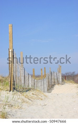 A fenced pathway through the sand dunes - stock photo