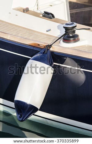 A fender suspended between a boat and dockside for protection/ Maritime fender - stock photo