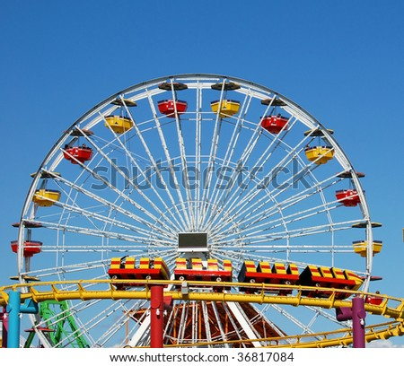 a ferris wheel and rollercoaster at an amusement park - stock photo