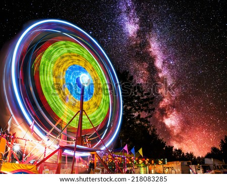 A Ferris wheel taken at night under the stars using a long exposure to capture the circular motion of the lights.  Distant stars and milky way galaxy fill the background.  - stock photo
