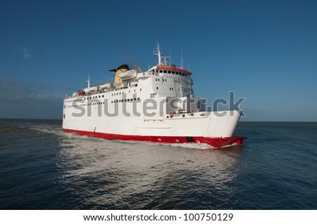 A ferry boat / transportation ship cruises over the sea - stock photo