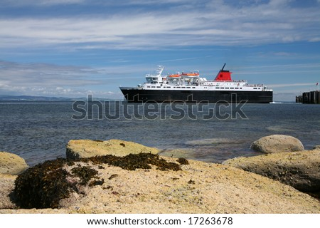 A ferry leaving port off a Scottish island - stock photo