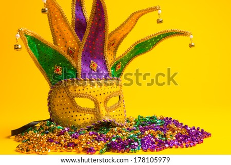 A festive, colorful group of mardi gras or carnivale mask on a yellow background.  Venetian masks. - stock photo