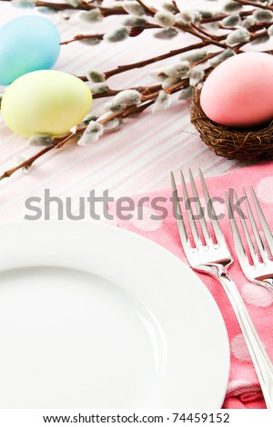 A festive pastel pink table setting is decorated for Easter with traditional dyed eggs and pussy willows leaving ample copy space on a white plate - stock photo