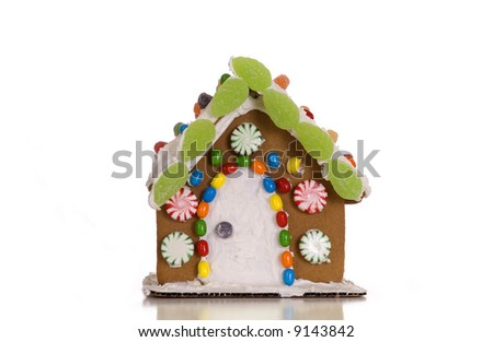 A festively decorated gingerbread house isolated against a white background. - stock photo
