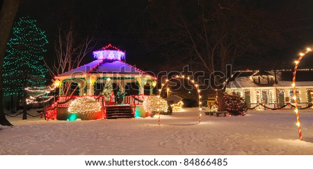 A festively lit small-town gazebo and train depot at Christmas - stock photo