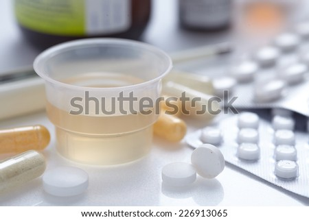a fever thermometer and tablets. symbolic photo for flu and colds - stock photo
