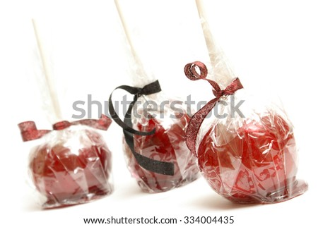A few candy apples wrapped in a clear plastic.