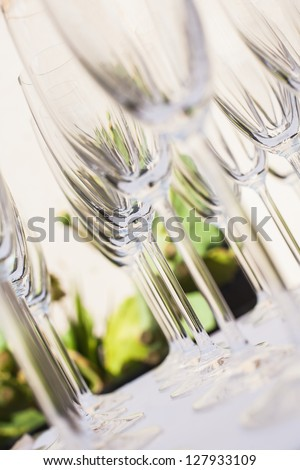 A few champagne glasses standing in a row and photographed from different angles. - stock photo