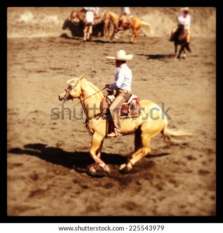 A few cowboys riding their saddled up horses. - stock photo