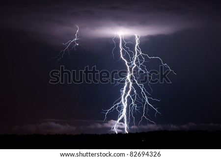A few elevated thunderstorms put down a few close and powerful shots of lightning. - stock photo