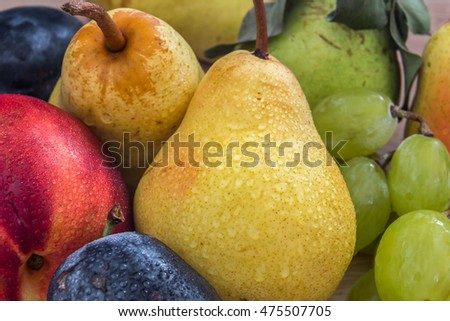 a few fresh bio pears, grapes, plums and nectarine  on the wooden table