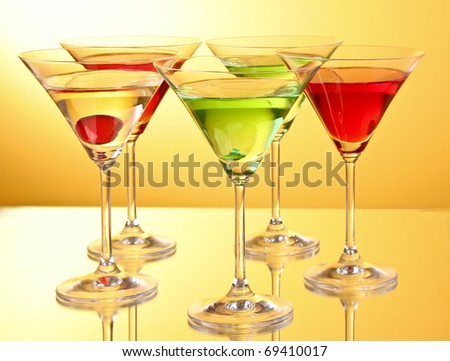 a few glasses of alcoholic drinks in a yellow-brown background - stock photo