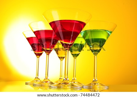 a few glasses of alcoholic drinks in a yellow-brown background