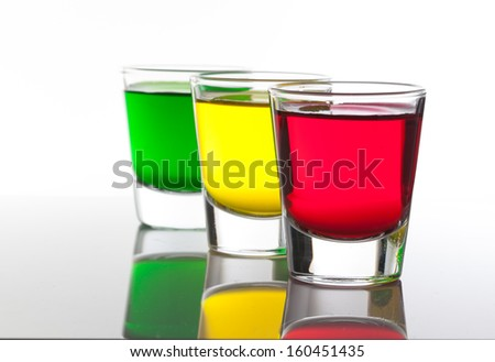 a few glasses of alcoholic drinks in red green yellow - stock photo