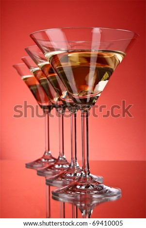 A few glasses of martini on a red background - stock photo