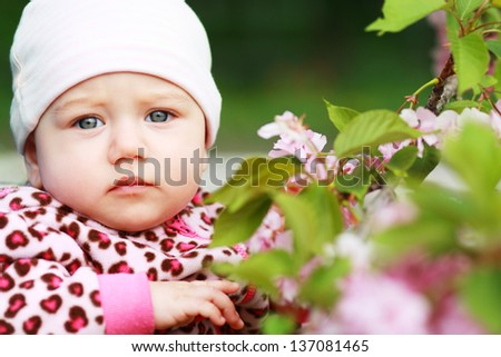 A few months old baby outdoor in the spring park - stock photo