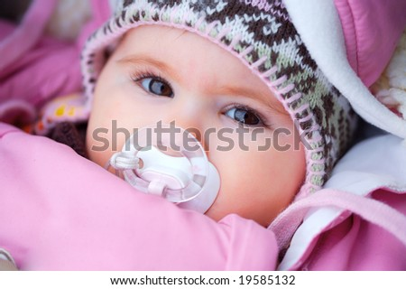 A few months old baby outdoor in warm clothes in a cold winter day. - stock photo
