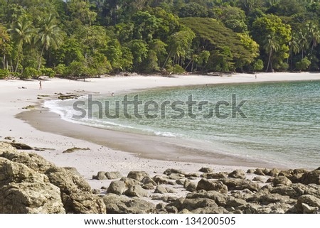 A few morning bathers on rainforest-lined Playa Manuel Antonio in Manuel Antonio National Park, Costa Rica - stock photo