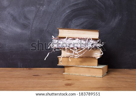 A few old books and one book with shredded paper instead of pages on a wooden table against a chalkboard. - stock photo